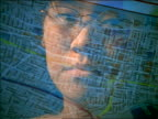 close up reflection of Asian woman with eyeglasses in computer screen looking at maps