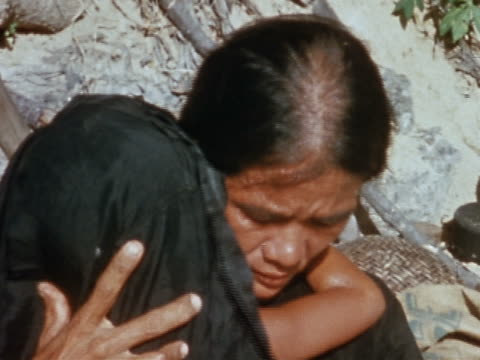 1967 close up sadlooking Vietnamese woman holding small child in her arms / Vietnam