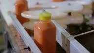 Close up sealed bottles of carrot juice moving along conveyor belt at juice factory