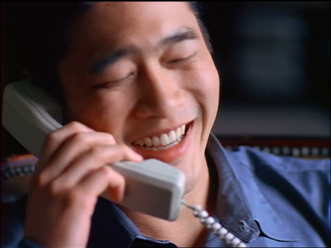 close up seated young Asian man talking + laughing on telephone