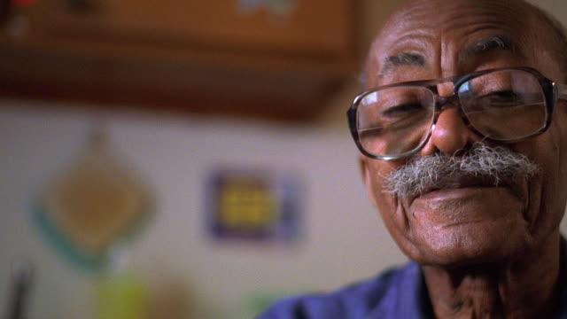 Close up senior Black man posing in kitchen