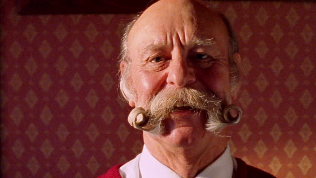 Close up senior British man with curled mustache making faces