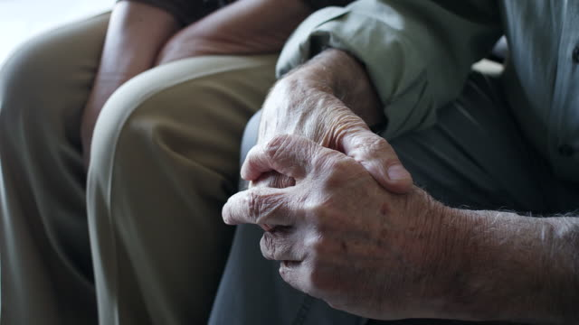 Close up, senior man clasped hands