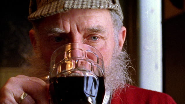 Close up senior man with mustache drinking pint of stout beer