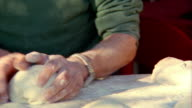 Close up senior man's hands kneading and shaping dough outdoors / Provence, France