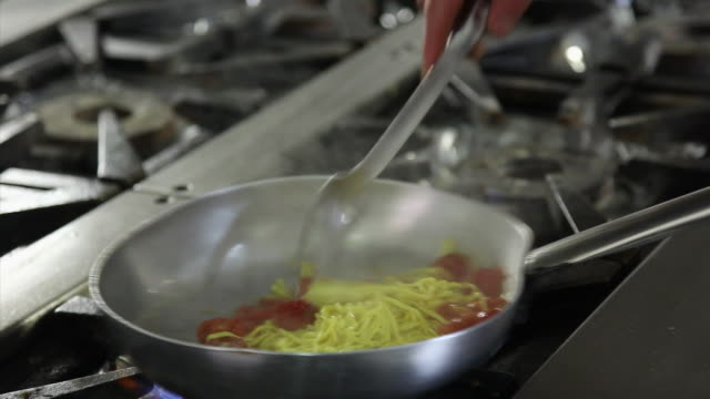 Close up shot of a chef cooking tomato and basil spaghetti into pan