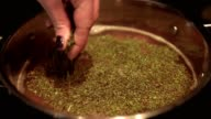 Close up shot of a female hand adding spices herbs to a meal in a cooking pot on the hot plate