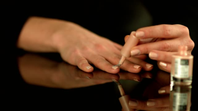 Close up shot of a female hands doing manicure applying nail polish to fingers