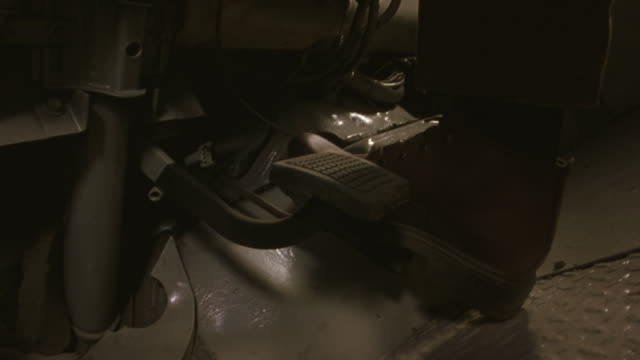 Close up shot of a man's foot switching back and forth between the gas and the brake pedals in a truck.