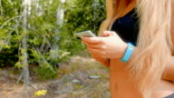 Close up shot of a working out girl who is using her smart phone outdoors