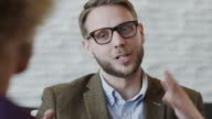 Close up shot of bearded businessman gesturing and talking to co-worker / Provo, Utah, United States,
