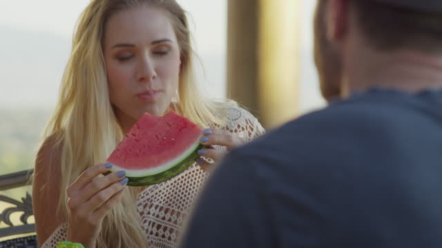 Close up shot of couple eating watermelon slices / Cedar Hills, Utah, United States