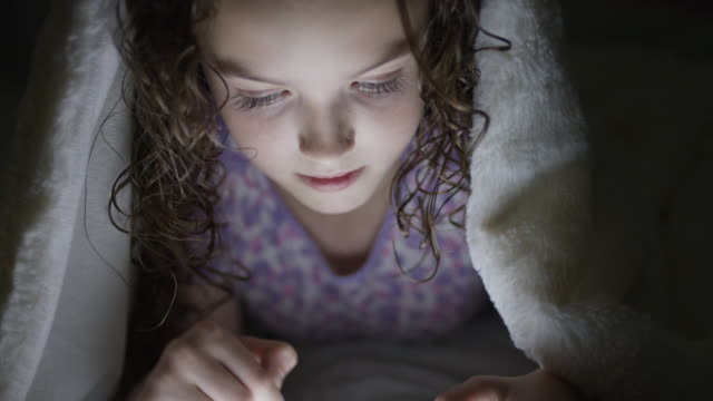 Close up shot of girl typing on digital tablet in bed under blanket at night / Provo, Utah, United States