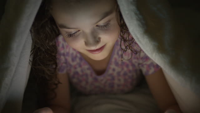 Close up shot of girl watching digital tablet in bed under blanket at night / Provo, Utah, United States