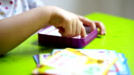 Close up shot of little girl's hands lifting and placing cards