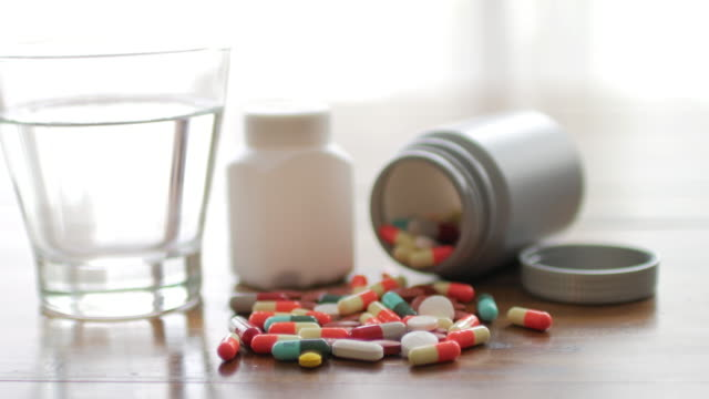 Close up shot of medicine capsule with wooden table background with drinking water , Dolly shot right to left movement