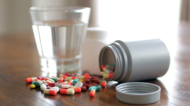 Close up shot of medicine capsule with wooden table background with drinking water