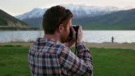 Close up shot of Photographer at mountain lake