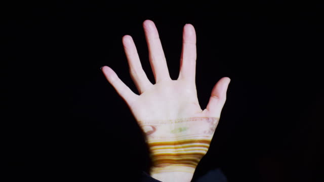 'Close up shot of projections of money on hand / Cedar Hills, Utah, United States'