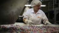 Close up shots of Dum Dum Lollipops being wrapped with wrapping paper during the manufacturing process at the Spangler Candy Company plant in Bryan...