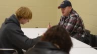 Close up shots of job applicants filling out applications at a jobs fair in Illinois Employees speak with potential employees at a Jobs Fair in...
