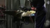 Close up shots of sparks flying as a sander smooths the edge of a large propeller blade A worker wearing a welders mask welds a propeller core at the...