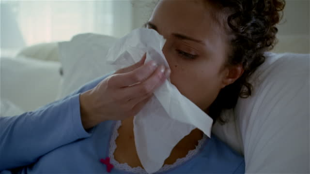 Close up sick woman lying in bed, coughing, blowing nose, and rubbing eyes/ Solebury, Pennsylvania