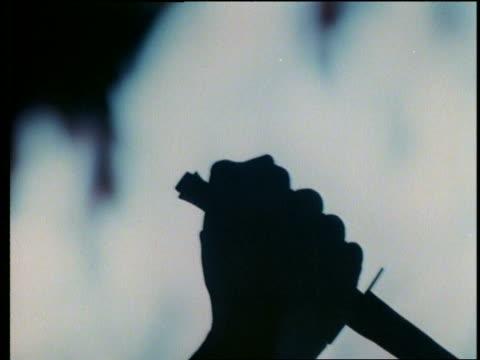close up silhouette of hand raising a dagger