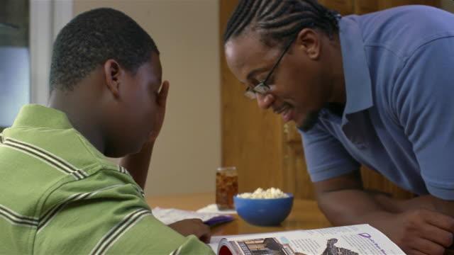 Close up single father helping son with homework/ San Antonio, Texas