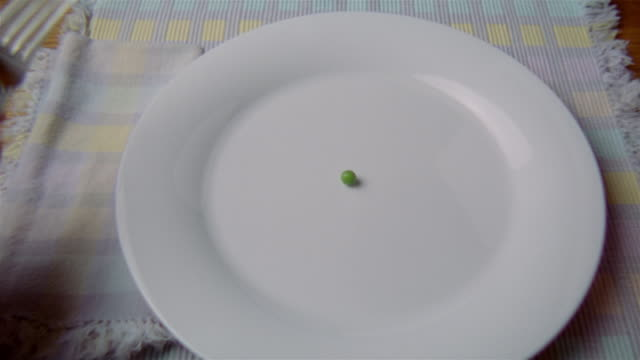 Close up single green pea on plate being cut with a knife and fork