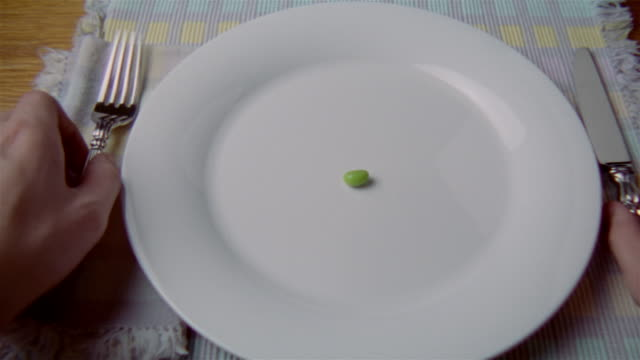 Close up single lima bean on plate being cut with a knife and fork