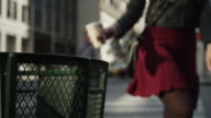 Close up slow motion of woman throwing coffee cup in city garbage can / New York City, New York, United States