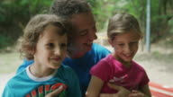 Close up slow motion panning shot of father and children laughing in park / Plovdiv, Bulgaria
