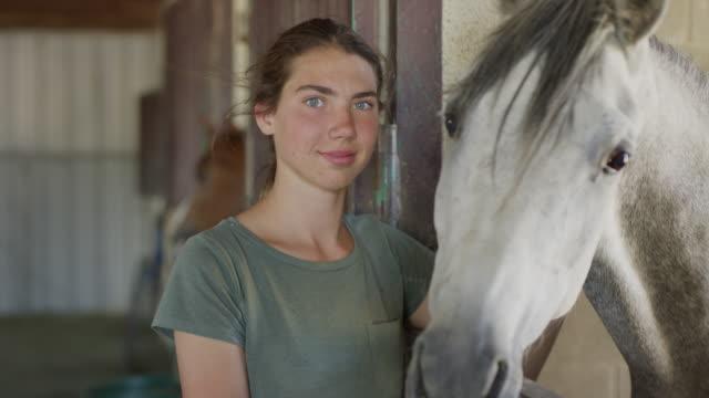 Close up slow motion portrait of girl petting horse / Lehi, Utah, United States