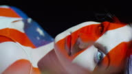 Close up slow motion shot of American flag projections on woman‰'s face / Cedar Hills, Utah, United States