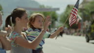Close up slow motion shot of family watching parade / American Fork, Utah, United States