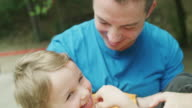 Close up slow motion shot of father cradling son in park / Plovdiv, Bulgaria