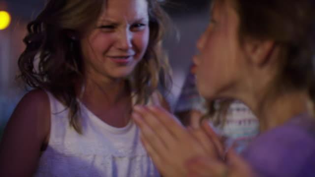 Close up slow motion shot of girls dancing at amusement park / Pleasant Grove, Utah, United States
