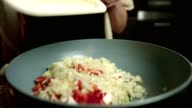 Close up slow motion shot of hands adding chopped onion and red pepper to a meal cooking in frying pan