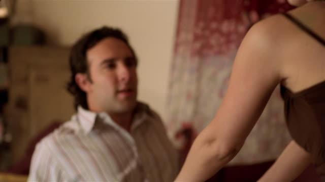 Close up slow motion woman pushing man onto sofa / straddling man / kissing