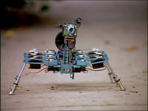 close up small eight-legged spider robot slowly walking on ground