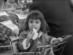 B/W 1963 close up small girl sitting in shopping cart eating banana / grocery store / documentary