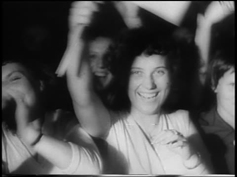 B/W 1958 close up smiling female fans waving to camera at gala premiere / Berlin Germany / newsreel