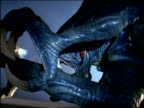 close up snarling alien monster turning to face + coming toward camera