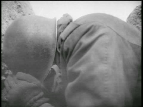 B/W 1955 close up soldier bent over shielding face during atomic testing / Nevada / documentary
