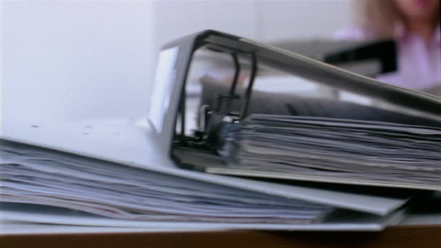 Close up stack of binders on desk / medium shot pan to disheveled businesswoman