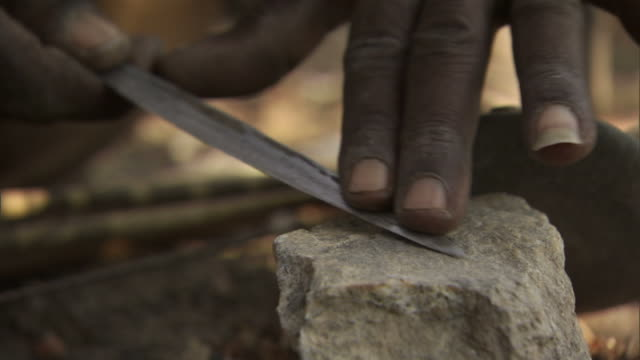 Close Up static - A hand sharpens a knife on a whetting stone. / Hadza, United Republic of Tanzania
