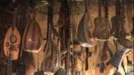 Close Up, static - A merchant displays a variety of guitars and other stringed instruments / Egypt