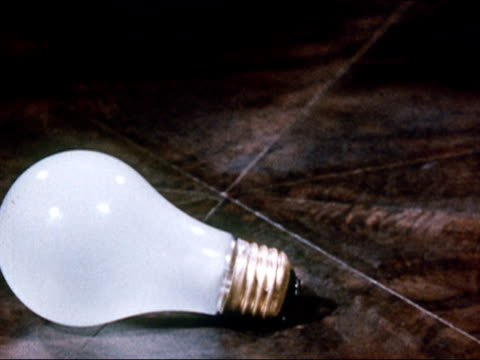 1949 Close up stop motion animation light bulb laying on its side/ standing upright and turning on/ AUDIO