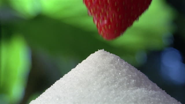 Close up strawberry being dipped into pile of sugar